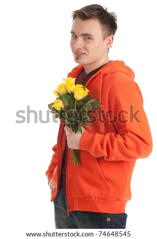 young handsome man in orange sweatshirt holding a yellow roses - stock photo