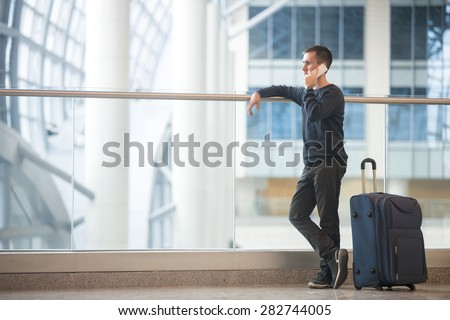 Young handsome man in 20s standing beside glass wall in modern airport terminal, talking on smartphone, travelling with luggage bag, wearing casual style clothes, side view, copy space