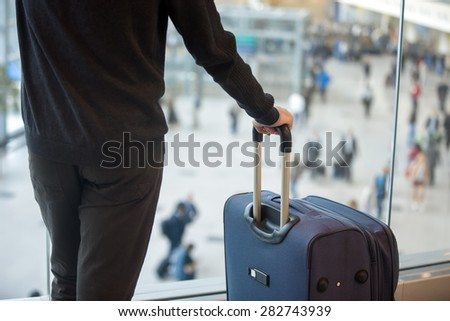 Young handsome man in 20s waiting for flight, standing in modern airport terminal with crowd on background, holding handle of luggage bag, wearing casual clothes, rear view, close up - stock photo