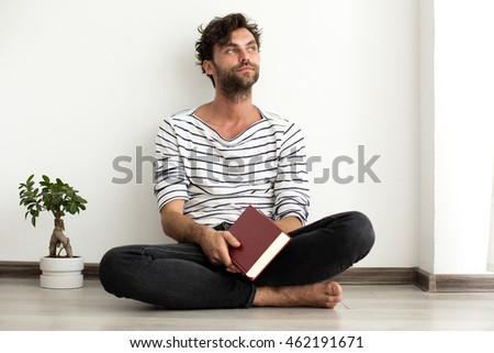 young handsome man in stripped shirt reading a book white standing on the floor next to a plant