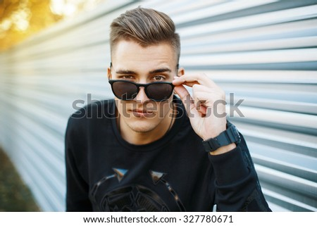 Young handsome man in stylish black clothes looking through sunglasses. - stock photo
