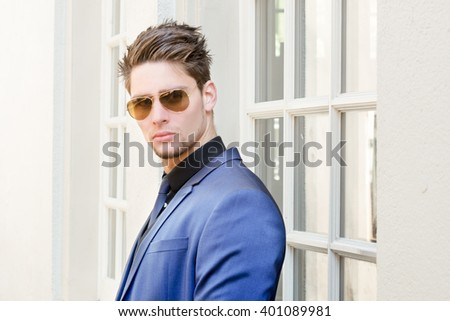 Young handsome man in stylish blue suit looking through sunglasses - Attractive confident male model  - stock photo