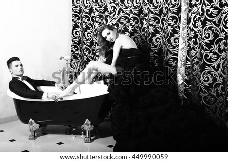 young handsome man in suit and bow with pretty sexy woman in elegant evening dress with skirt and long curly hair sitting in bath, black and white
