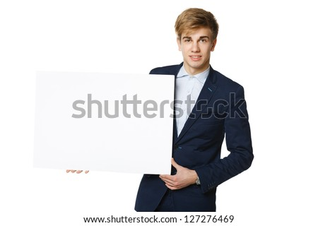 Young handsome man in suit holding blank whiteboard, over white background