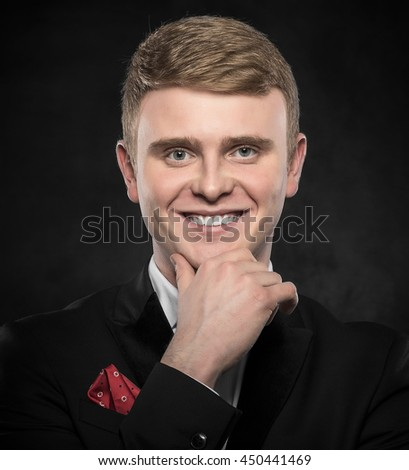 Young handsome man in suit on dark background. - stock photo