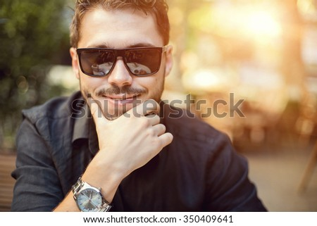 Young handsome man in sunglasses on the sunset.
