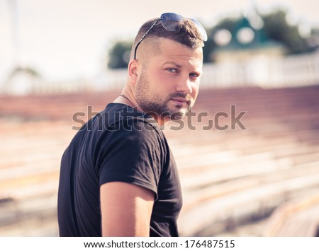 young handsome man in sunglasses poses  on outdoors. dressed casual