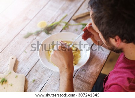 Young handsome man in the kitchen eating salmon tagliatelle   - stock photo