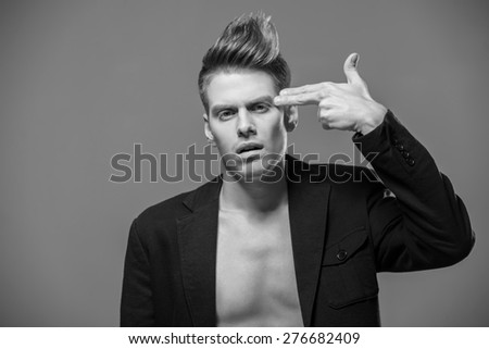 Young handsome man in tuxedo holding fingers on his head. Black and white fashion portrait. - stock photo