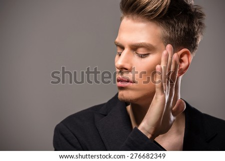 Young handsome man in tuxedo posing in the studio on dark background. Fashion portrait. - stock photo