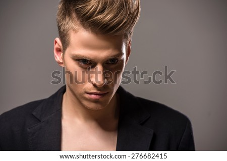 Young handsome man in tuxedo posing in the studio on dark background. Fashion portrait.