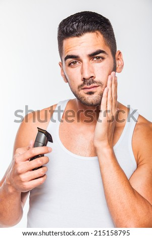 young handsome man in white shirt trimming his beard with a trimmer - stock photo
