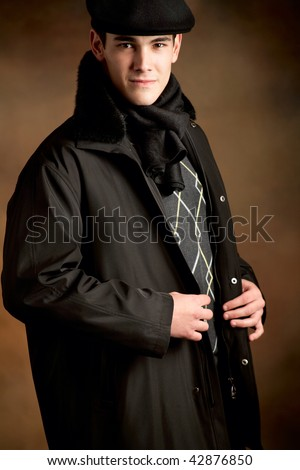 young handsome man in winter clothes with beret - stock photo