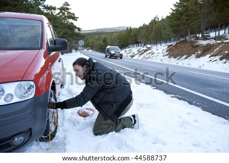 Young handsome man installing snow chain on his car. - stock photo