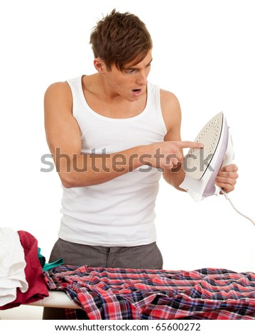 young handsome man ironing clothes - stock photo