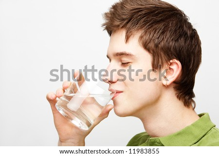 young handsome man is drinking mineral water - stock photo