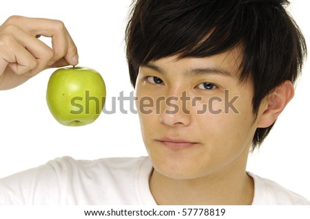 Young handsome man is holding a green apple