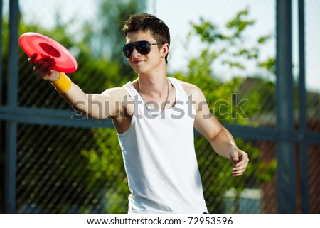 young handsome man is playing frisbee in the park - stock photo