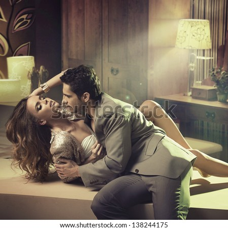 Young handsome man kissing his girlfriend - stock photo