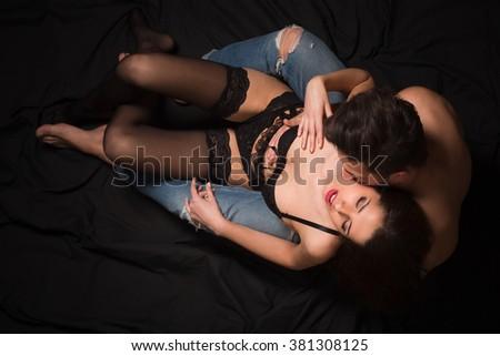 Young handsome man kissing his girlfriend's neck over dark. Sexy girl wearing underwear and having satisfaction in studio. - stock photo