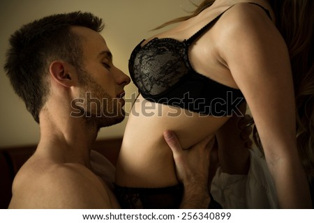 Young handsome man kissing his pretty slim woman's body - stock photo
