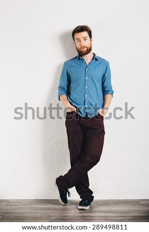 Young handsome man leaning against a white wall - stock photo