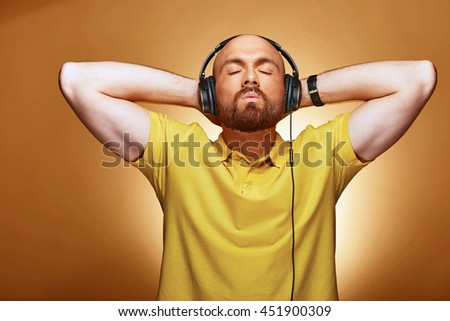 Young handsome man listen to the music with earphones and closed eyes
