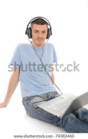 young handsome man listening to music in headphones from computer. isolated - stock photo