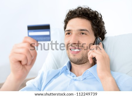 Young handsome man looking on credit card and talking on modern mobile phone. Studio shot.