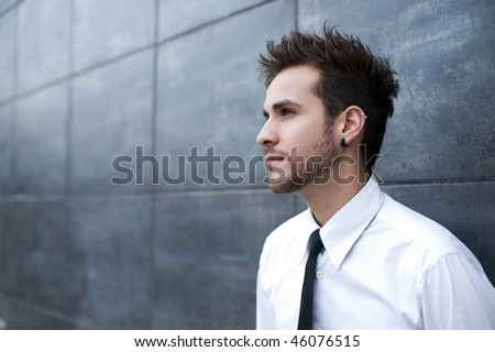 Young handsome man looking thoughtful (piercing in ear) - stock photo