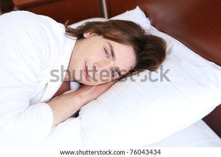 young handsome man lying in a bed at home