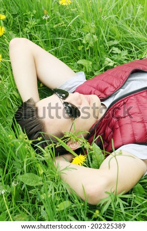 Young handsome man lying on the grass - stock photo