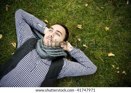 Young handsome man lying over green grass - stock photo