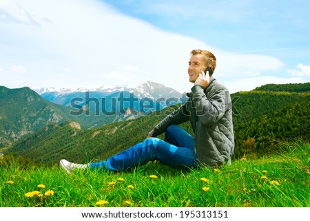 Young handsome man making a call on his mobile sitting in grass on green field. Casual wearing man talking on Cellphone outdoor. Mountains. Communication concept. Freedom. Vacation. Technology. - stock photo