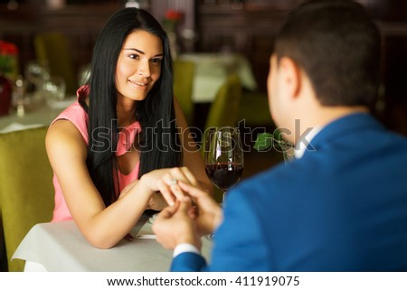 young handsome man making a proposal to his girlfriend, a young couple on a date at the restaurant