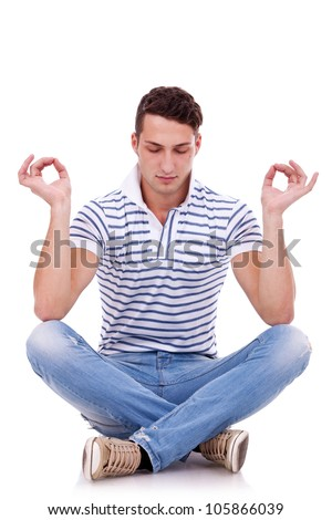 young handsome man meditating in lotus position on white background - stock photo