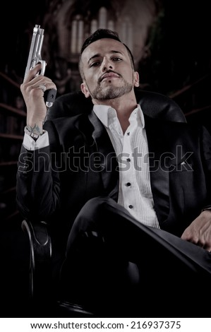 Young handsome man model mobster spy hitman killer sitting in a chair pointing gun up starring at camera - stock photo