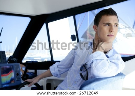 Young handsome man on a yacht boat interior in summer - stock photo