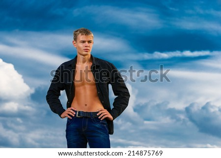 Young handsome man on the beach. Looks thoughtfully into the distance. The sky in the background. Summer vacation concept.