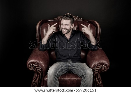 young handsome man or sexy guy with trendy beard on happy smiling face sitting on luxury brown leather chair in fashionable jeans and shirt in studio on black background