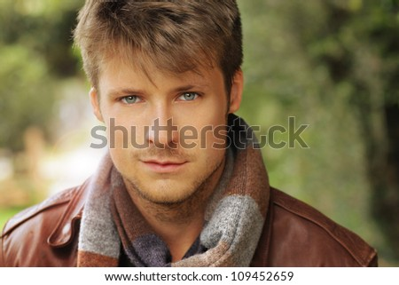 Young handsome man outdoors in fall clothing with autumn natural surroundings - stock photo