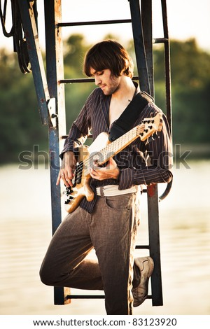 young handsome man play guitar, outdoor shot by the river in harbor - stock photo