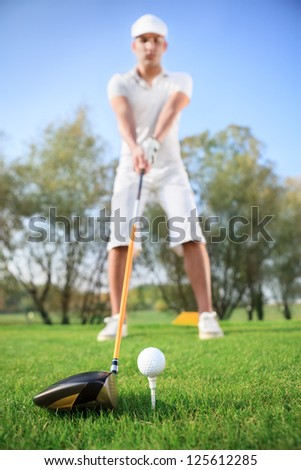 Young handsome man playing golf