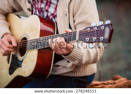Young handsome man playing guitar - stock photo