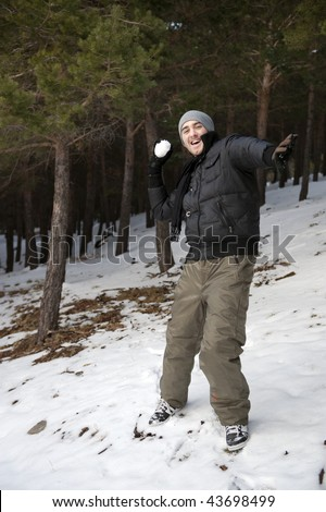 Young handsome man playing snowball in forest. - stock photo