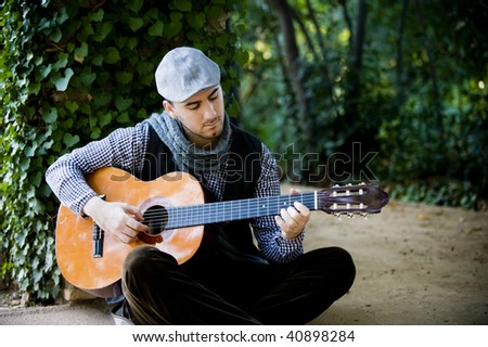 Young handsome man playing spanish guitar in green garden - stock photo