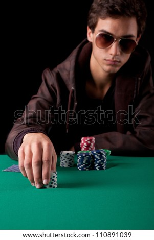 Young handsome man playing texas hold'em poker - stock photo