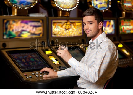 young handsome man playing the slot machine holding drink - stock photo