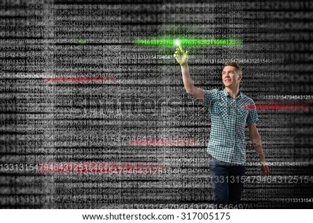 Young handsome man pointing at binary digital touchscreen - stock photo
