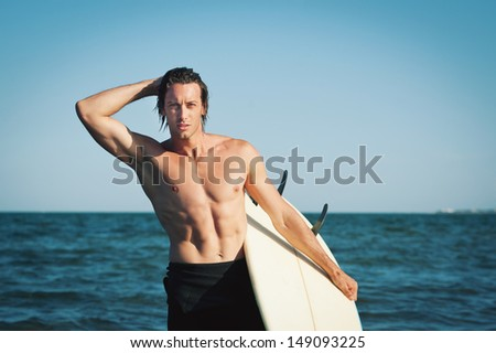 Young handsome man portrait at the sea with surfboard.  - stock photo